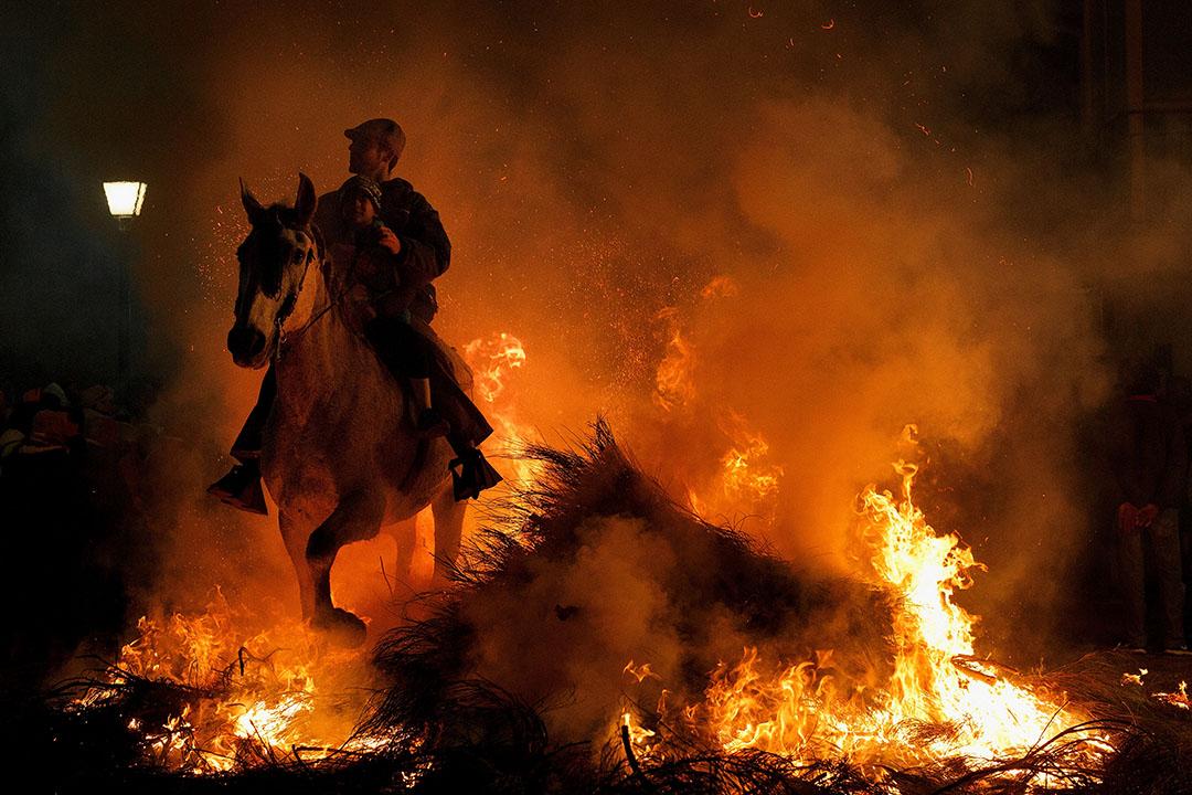 2017年1月16日,西班牙聖巴托洛梅,一名男子與小孩騎在馬上,於Las Luminarias'節日期間跳過冓火堆。