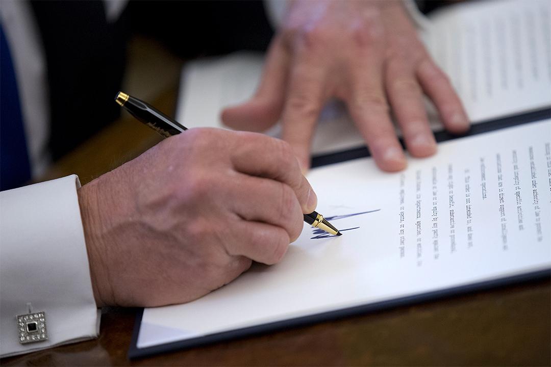 美國總統特朗普在白宮橢圓形辦公室簽署五項行政命令,其中一頂是限制移民。