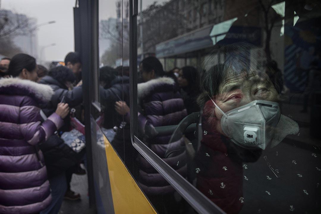 2016年12月12日,北京,一名婦人在公車上帶著口罩。
