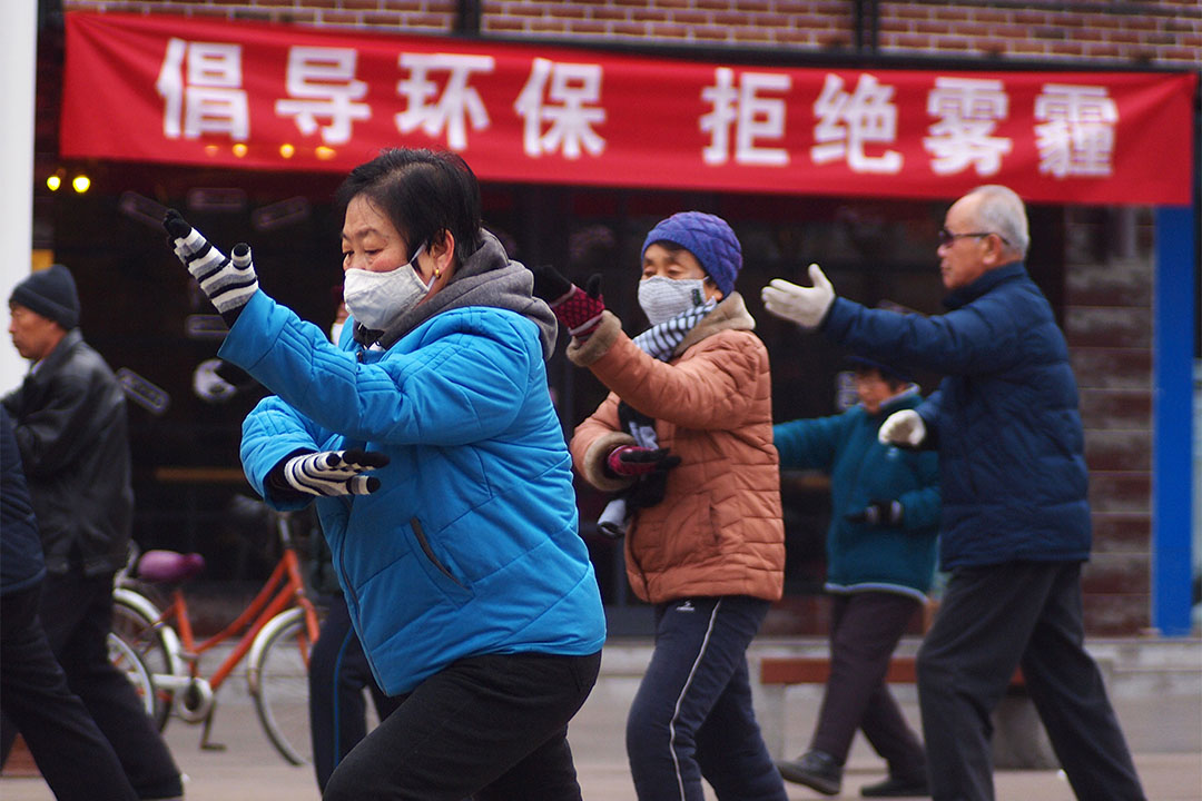 2017年1月10日,山西省臨汾市,市民一大早在鼓樓廣場進行晨練,背後的門店上懸掛著倡導環保 拒絕霧霾的紅色標語。