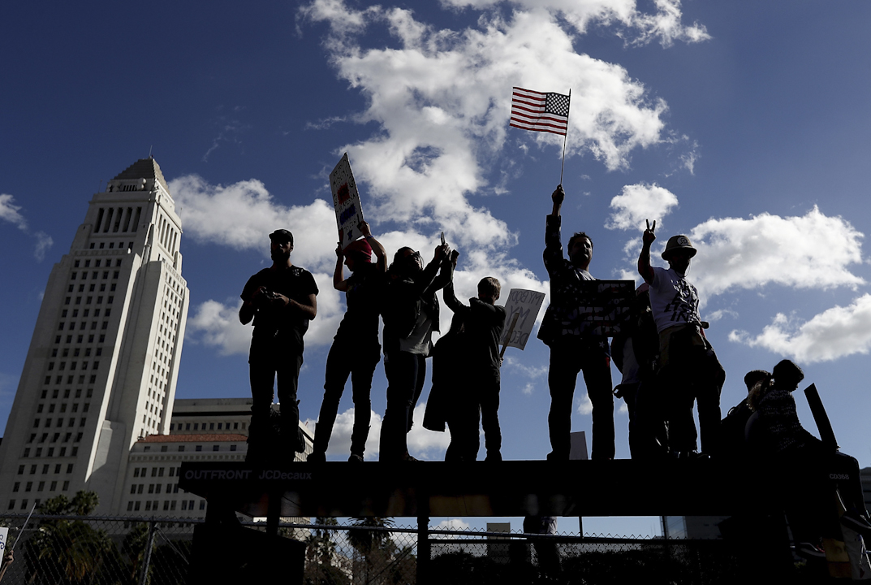 在美國加洲洛杉磯,有抗議者爬上巴士站上高舉標語牌。