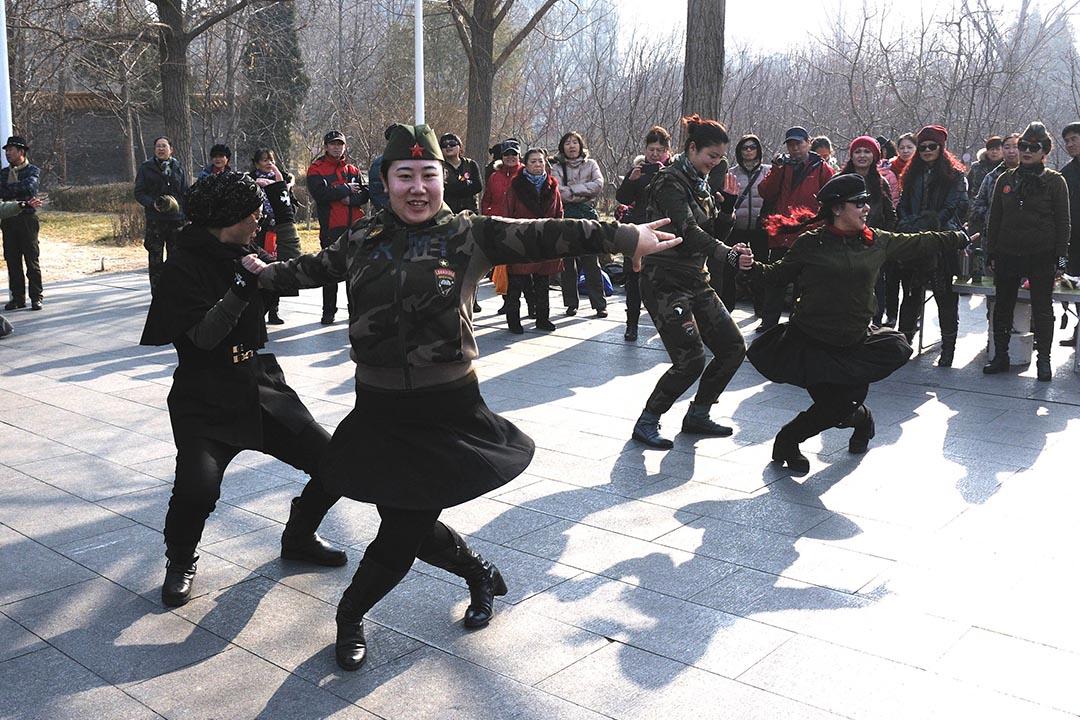 北京陶然亭公園,大媽們身穿迷彩製服,頭戴貝雷軍帽,盡情舞動展現風采。