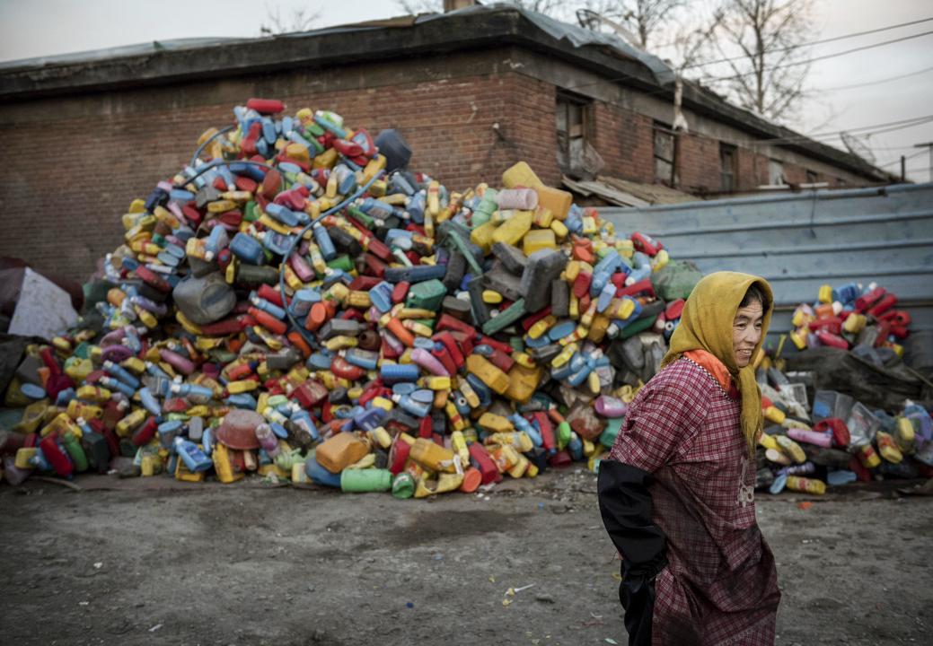 中國北京,工人在廢棄回收村經過,這個村莊主要由周邊省份的貧困家座組成,這回收廢棄村收集成千上萬的塑膠廢品 。