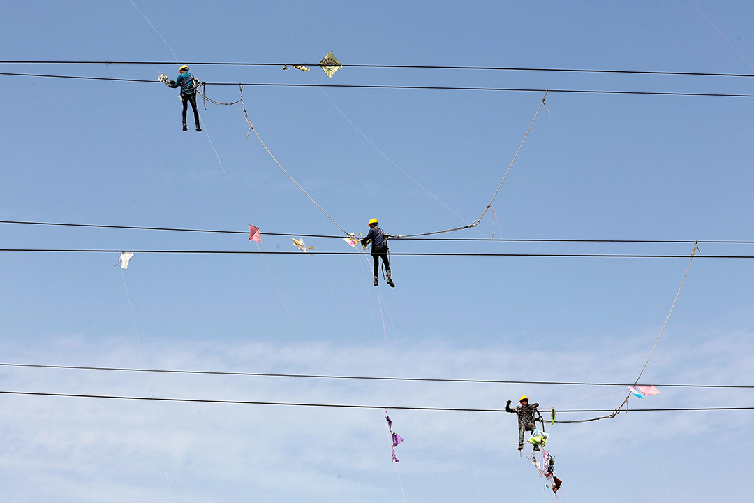 2017年1月16日,印度艾哈邁達巴德, 電力公司的工程人員於熱門放風箏季度後,清理於纏結於電纜上的風箏。