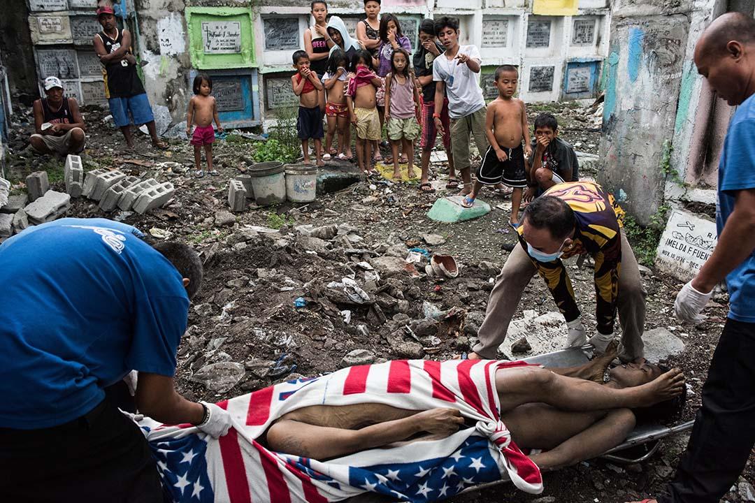 2017年1月24日,菲律賓馬尼拉,居住在公墓裡的棚戶區居民觀看無人認領的屍體被埋葬。自從去年7月開始打擊非法毒品活動以來,數以千計的吸毒者和販毒者在未經正常的法律審訊而被處決。
