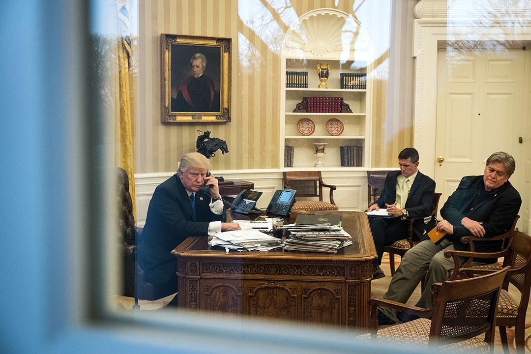 2017年1月28日,美國華盛頓,總統特朗普在白宮橢圓形辦公室與澳洲總理通話,旁邊為國家安全顧問弗林(右二)和白宮首席顧問班農(右)。當天,他另與日本,德國,俄羅斯和法國的領導人通話。