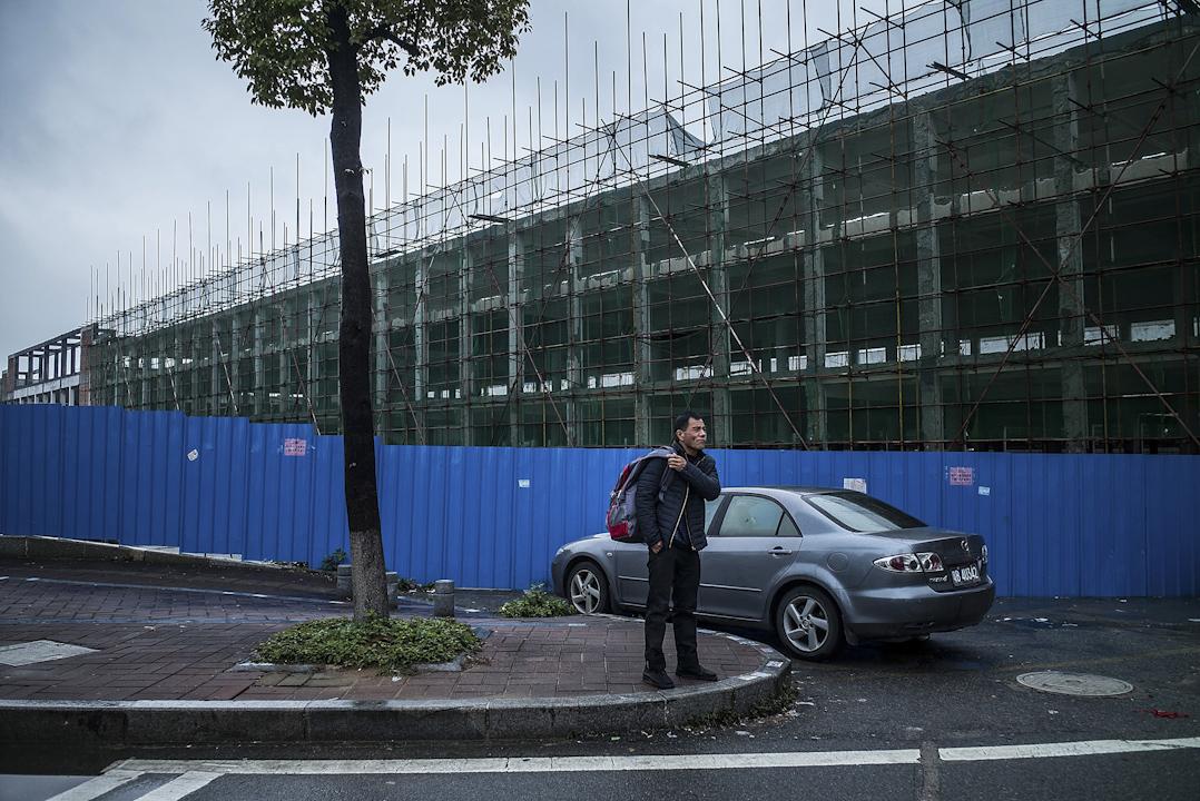 2016年1月27日,東莞厚街鎮一個廢棄的工地,一名男子正在經過。在東莞,許多製造中心工廠當時已經關閉,或開始減少員工人數。