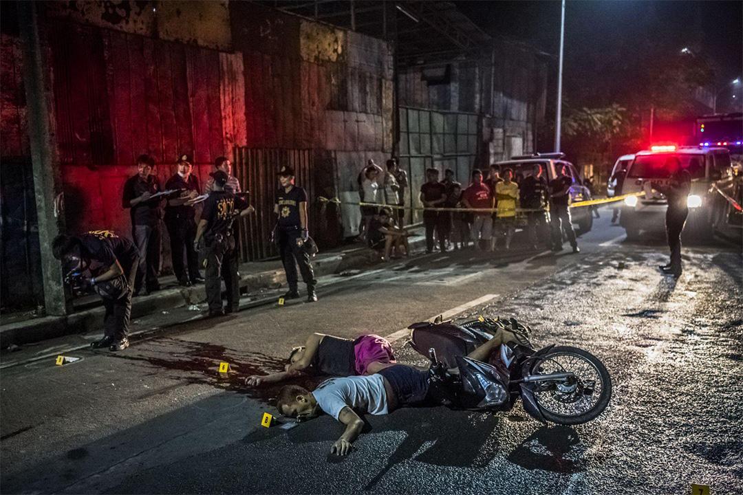 在菲律賓馬尼拉,兩名被不明身份的男子殺害的受害者的屍體伏在街道上,他們分別為48歲的Frederick Mafe和23歲的Arjay Lumbago。有警察於現場搜集證據。