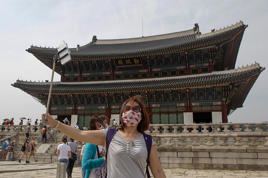 2015年,因「新沙士」影響了南韓旅遊業。圖為2015,遊客帶著口罩於南韓景點景福宮外拍照。