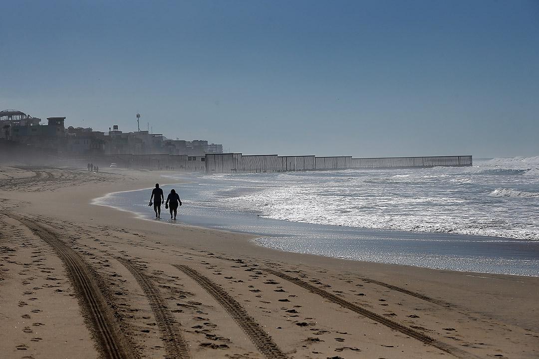 2017年2月4日,美國聖地亞哥,一對夫婦在鄰近美國與墨西哥邊界圍欄上的海灘散步。美國政府允許每個星期六及星期日開放邊境圍欄四小時,讓被驅逐出境或擁有混合移民身份( mixed immigration status) 的家人及朋友能夠於友誼公園(Friendship Park)相聚。