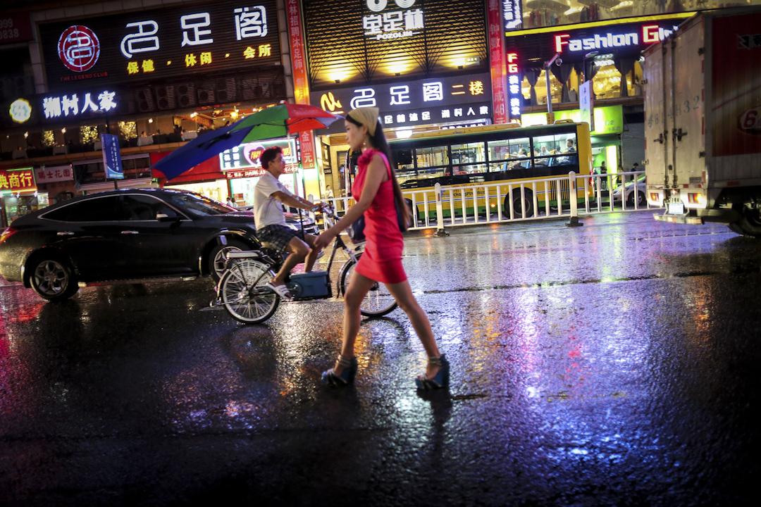 2014年8月,廣東東莞,一名女子走過空空的街頭。當年2月,東莞部分酒店涉黃的報道讓其成為全國焦點,其後東莞政府出動6525名警力,開展了大力度、大規模的掃黃行動。