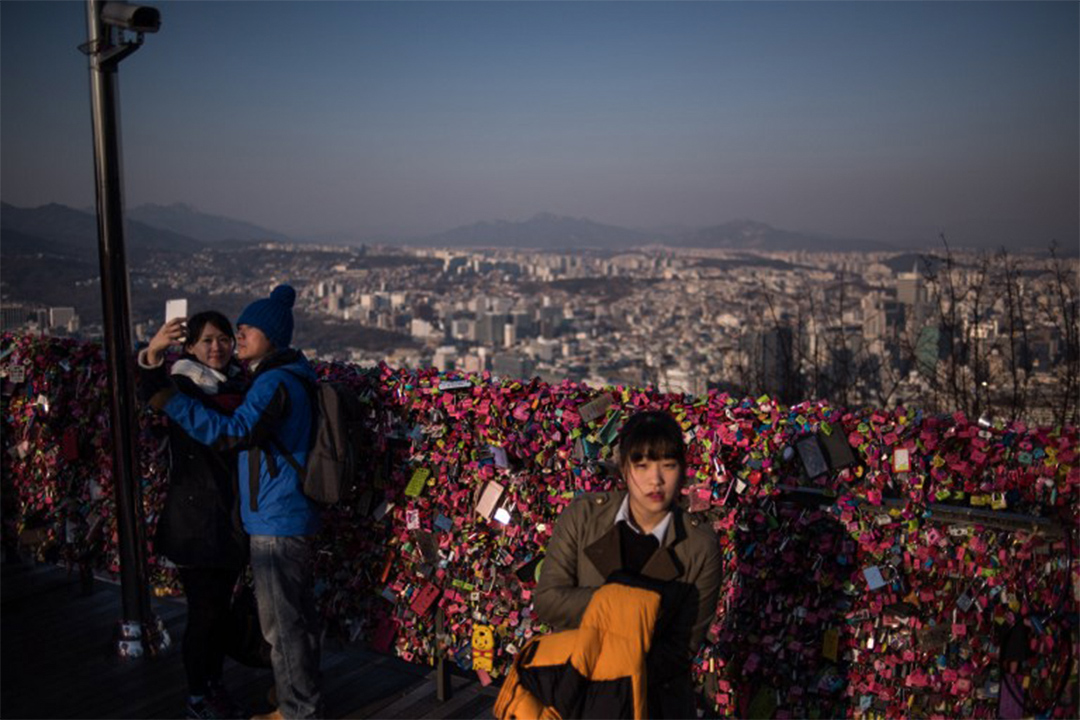 在南韓首爾塔上掛滿了情人鎖,浪漫氣氛吸引不少情侶拍照留念,一名女士於情侶前面走過。