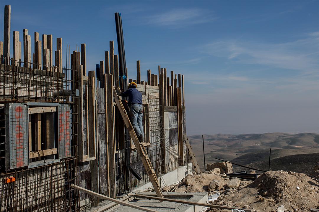 巴勒斯坦工人在以色列定居點工地建造房子。