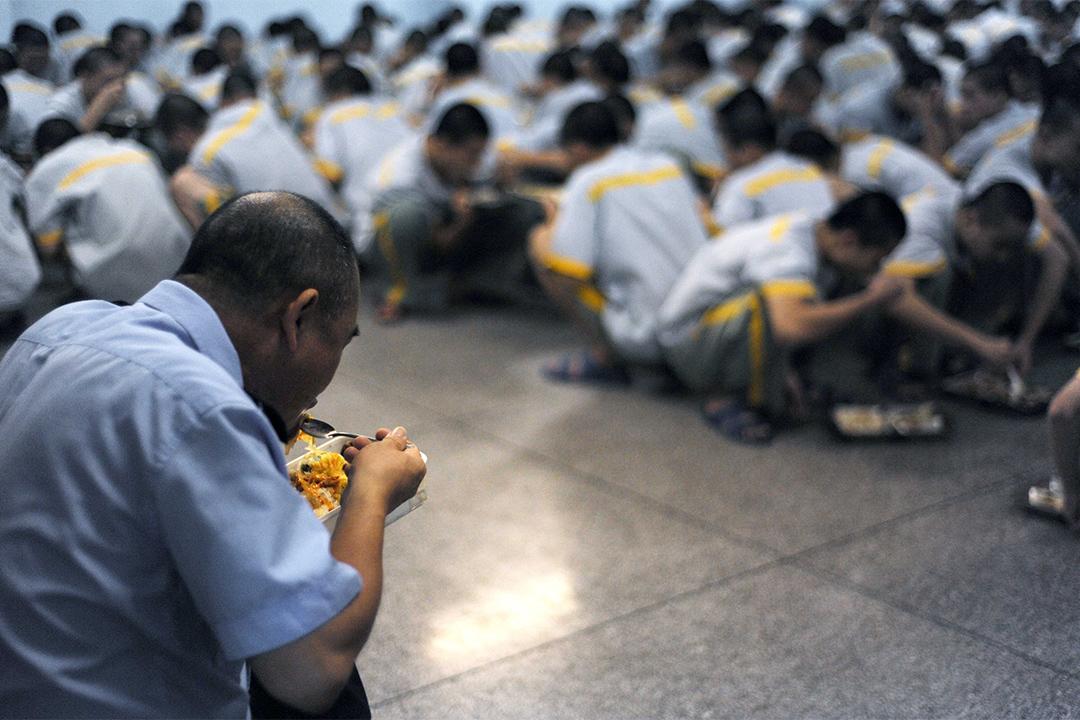監獄警察被稱為「特殊園丁」,肩負著教育和改造罪犯的責任。圖為獄警於傍晚一邊看管未成年犯一邊吃飯。