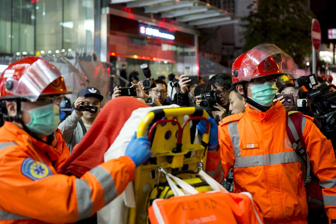 港鐵縱火案後,救護員在尖沙咀港鐵站外運送傷者往醫院治理。