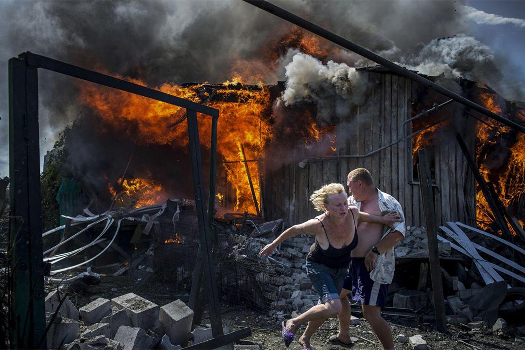 在烏克蘭Luhanskaya村莊發生空襲,平民正慌忙逃離火災區。