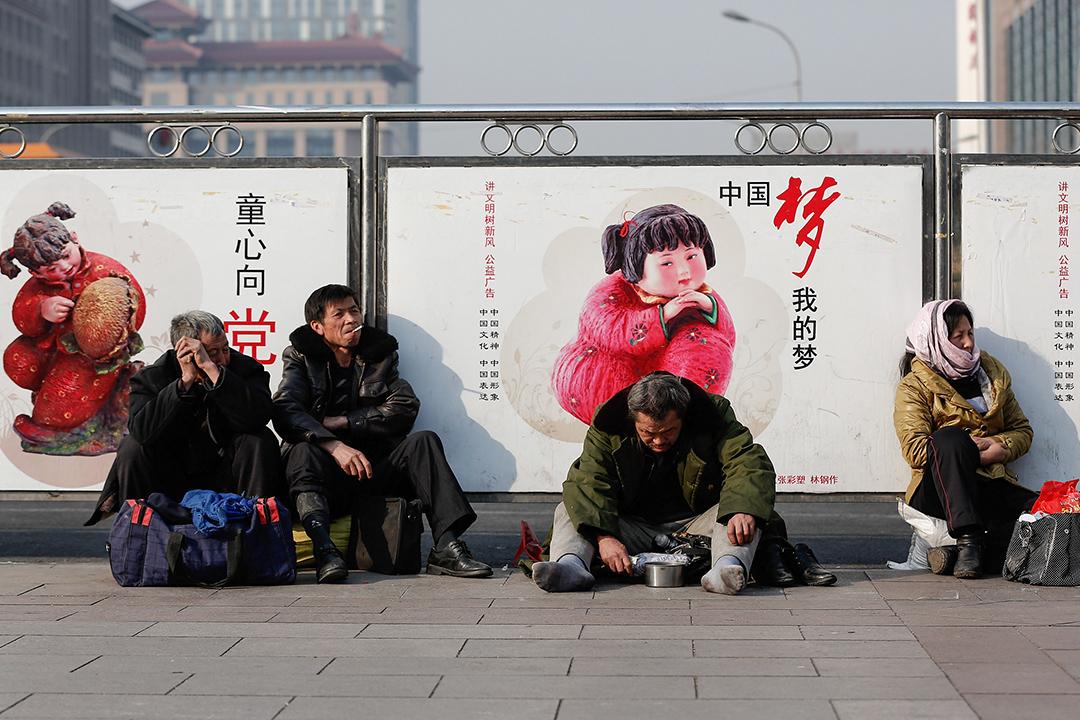 一名乞丐坐在北京火車站附近的街道。