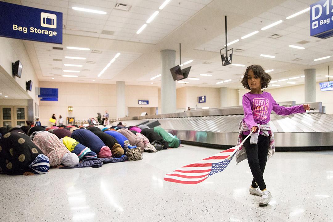 2017年1月29日,美國達拉斯, 一個年輕女孩在揮舞美國國旗,而在她的背後是一群前往機場抗議的婦女正祈禱中。