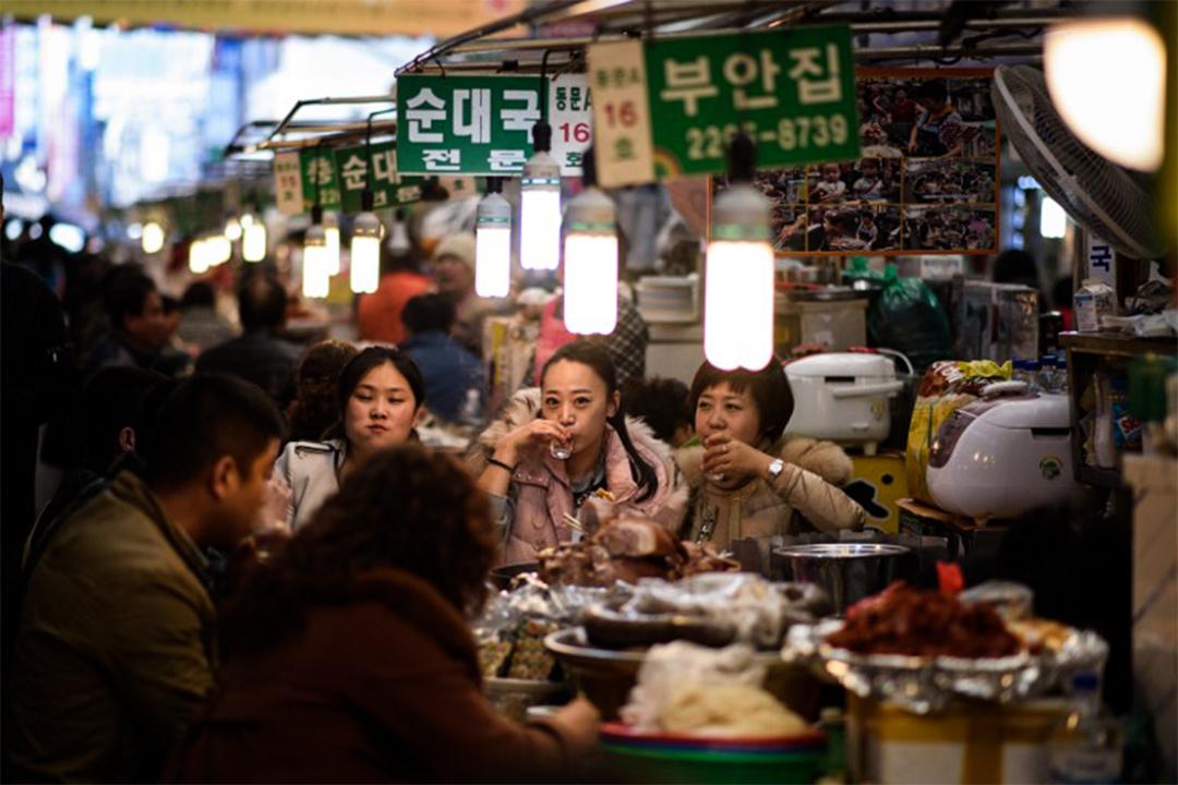 人們在首爾廣藏市場內喝韓國燒酒。