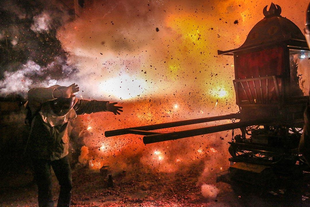 2017年2月10日,台灣台南,民眾戴著頭盔站於蜂炮發射旁邊。「鹽水蜂炮」是世界三大民俗慶典,相傳起源於清光緒11年7、8月間,當時瘟疫流行,人們於元宵夜燃放鞭炮向關公祈求平安,後演變成民間習俗,深信受過蜂炮洗禮,能消災解難,掃除穢氣。每年吸引數以萬計的旅客前往觀賞。