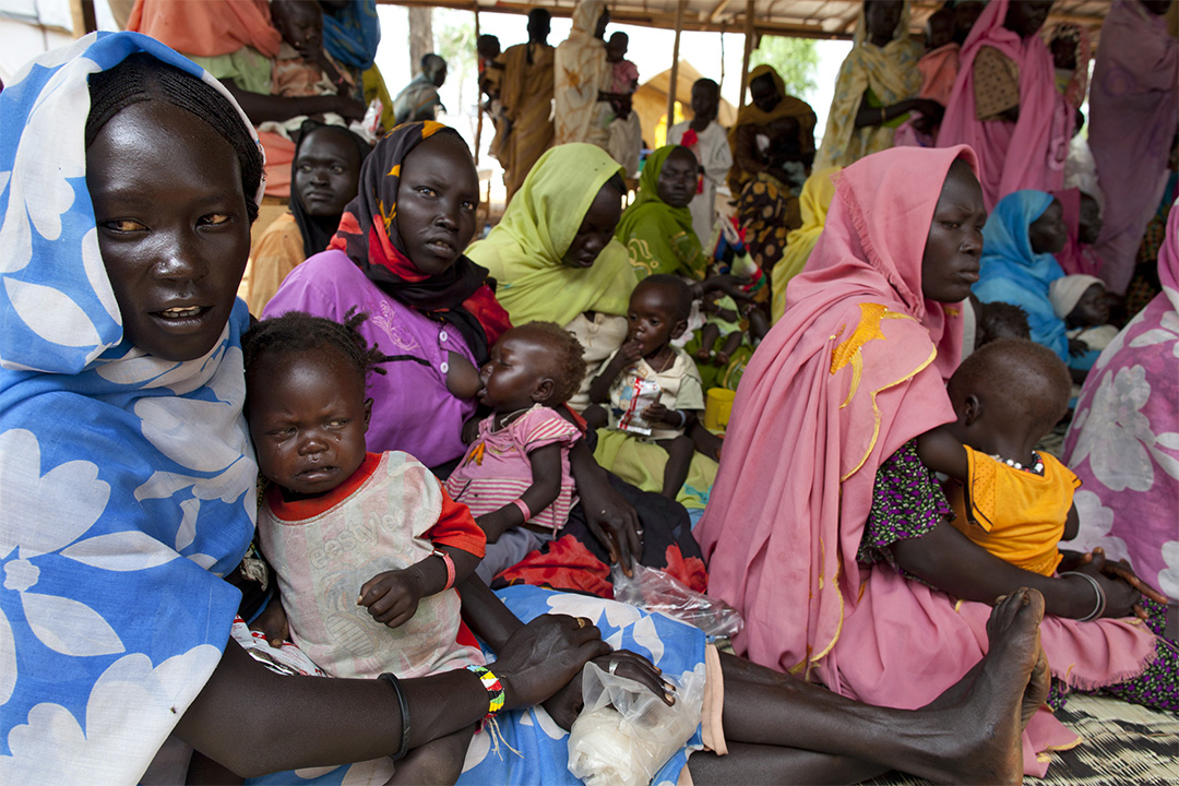 母親們抱著嬰兒在難民營內的臨時醫院,等待醫生為營養不良的嬰兒進行治療性餵養。