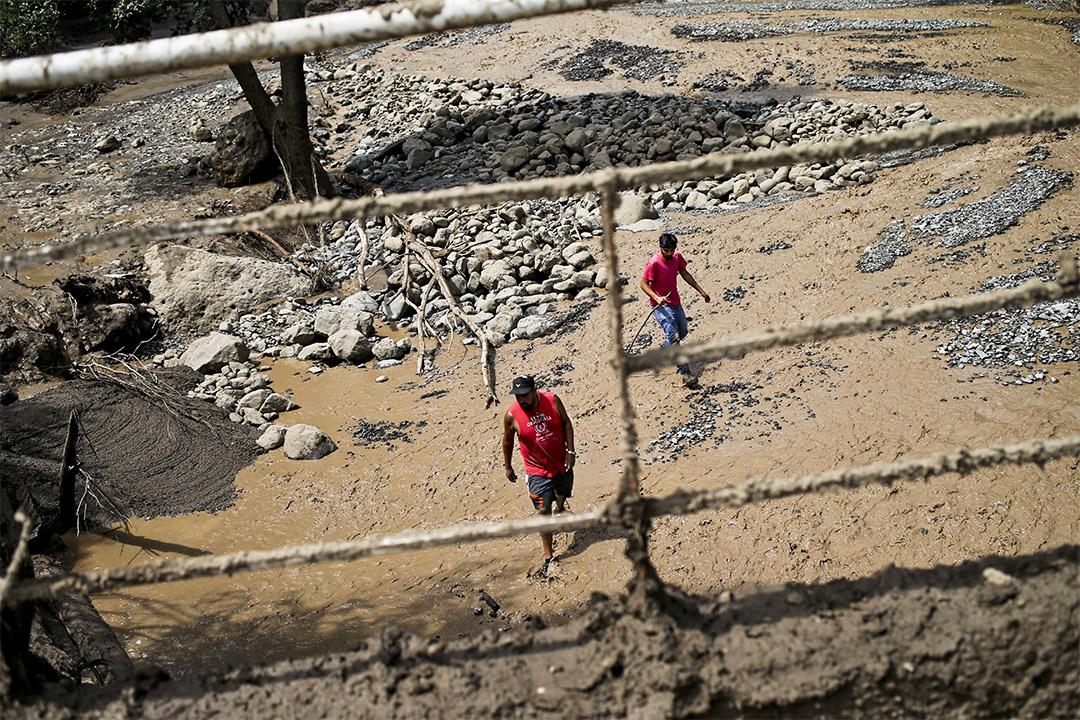 有人走過因洪水沖積的污泥。