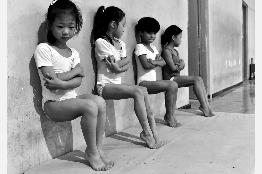 在中國徐州一所體操學校內,四名體操學生正在做腳趾壓力訓練。