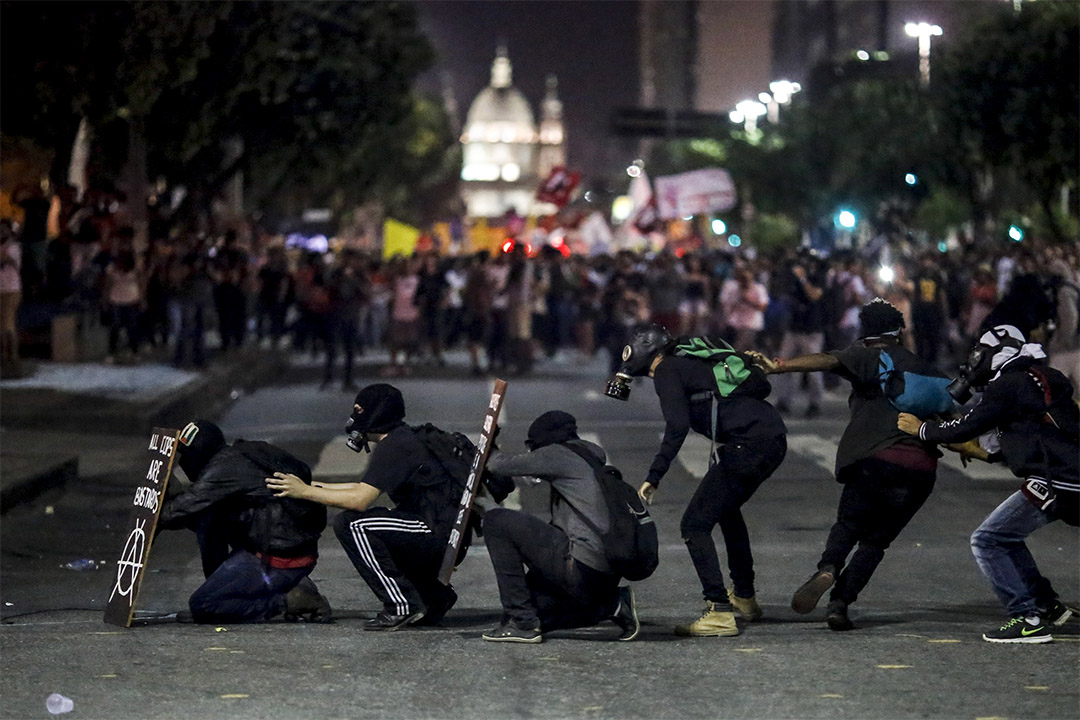 2017年3月15日,在巴西里約熱內盧,戴著防毒面具的示威者正與當地警察對峙。當地政府早前計劃將最低退休年齡由54歲上調至65歲,引發過萬人的大型示威反對養老金制度改革。