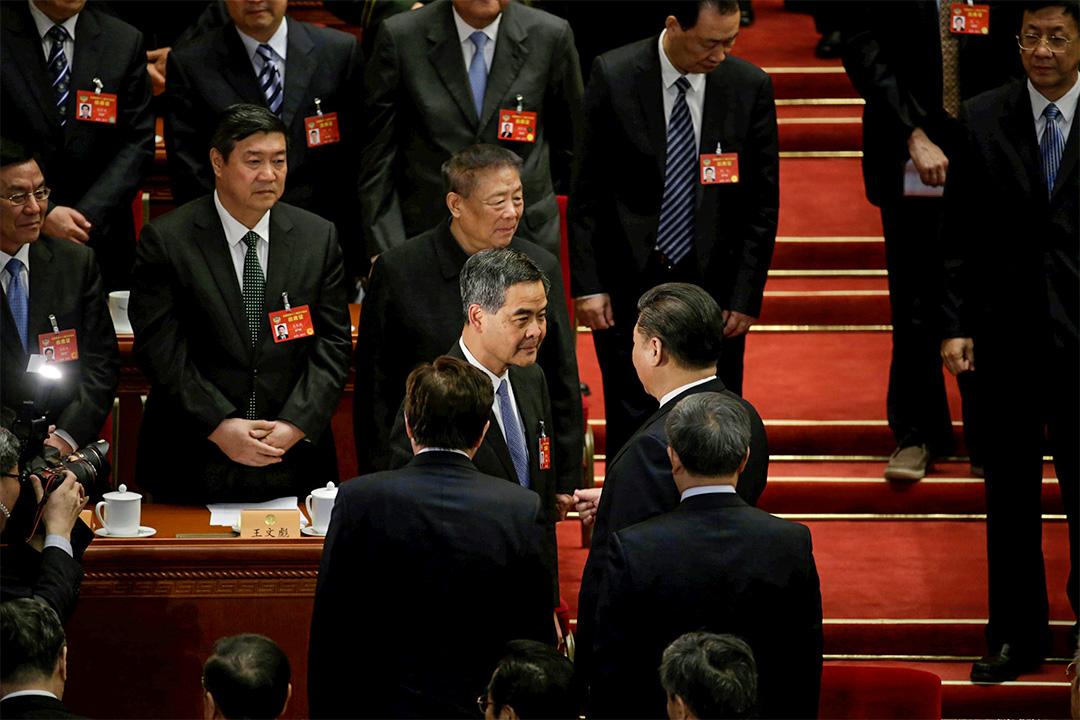 習近平與剛當選全國政協副主席的行政長官梁振英於會內握手。