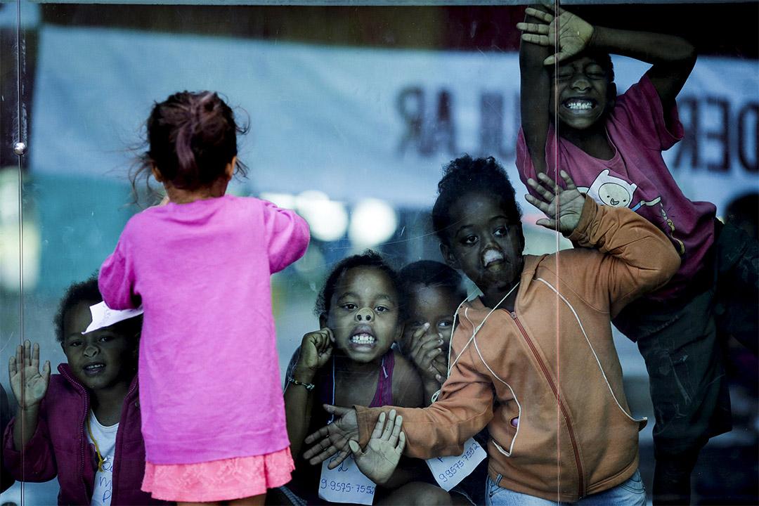 2017年3月15日,巴西巴西利亞,幾名小女孩貼近巴西財政部的玻璃窗口望出外面的反政府示威。該示威是為了反對政府的養老金制度改革。