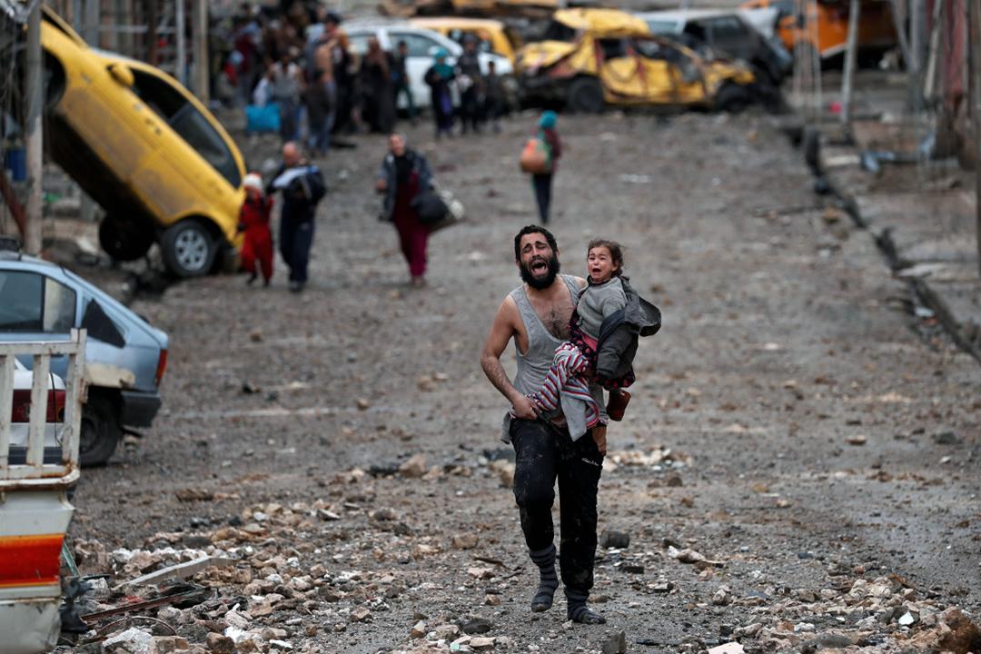 2017年3月4日,在伊拉克摩蘇爾的一場戰事中,一個男人帶著他的女兒,正從摩蘇爾ISIS控制的地區,奔向伊拉克特種部隊。