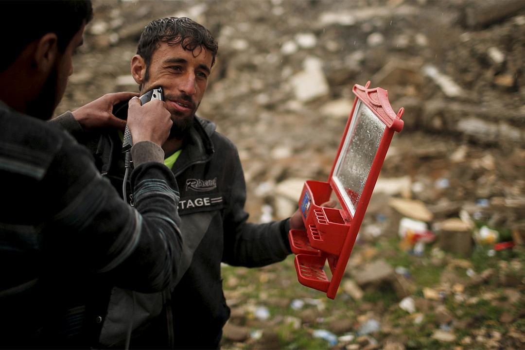 2017年3月15日,在伊拉克摩蘇爾以南的Hamam al-Alil營地,其中一名逃離家園的男士正在朋友的幫助之下刮鬍子。