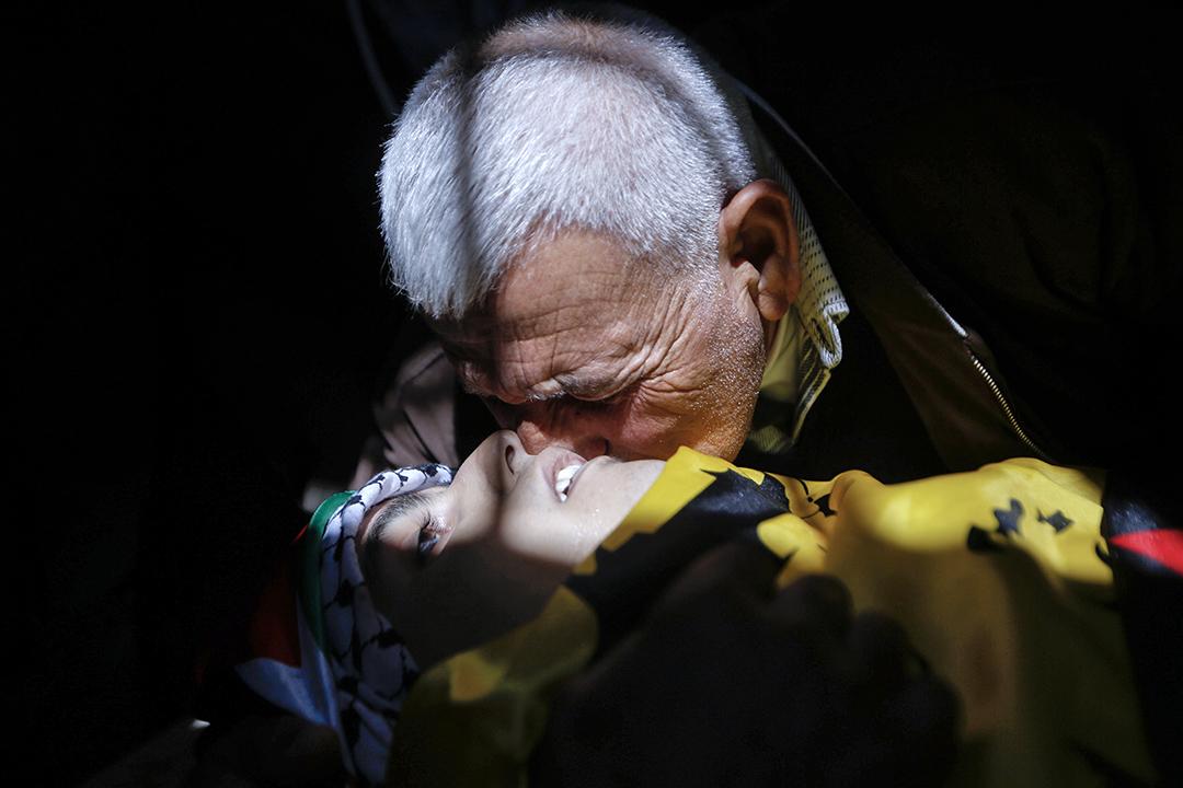 2017年3月24日, 在以色列拉馬拉附近的難民營, 葬禮期間, 一名親友吻別一個十七歲的巴勒斯坦青年Mahmoud Hattab。巴勒斯坦衛生部表示,以色列軍隊向約旦河西岸士兵們開火時,殺死了該青年,三名士兵受傷。