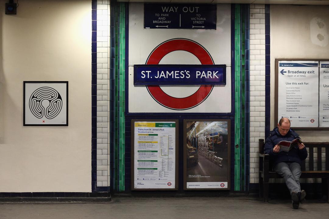 倫敦地鐵St James's Park Station月台上的一名男子,左方牆面上是英國藝術家Mark Wallinger的作品。
