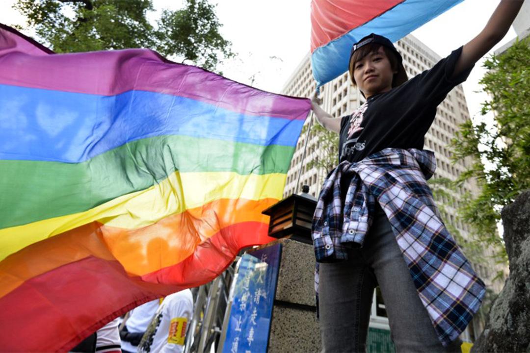 有台灣青年高舉象徵性少數群體(LGBT)的彩虹旗幟。
