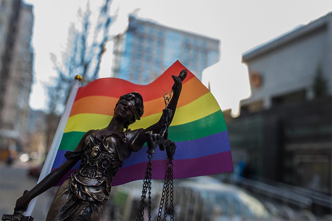 中國北京海澱區人民法院前,有人手拿彩虹旗及正義女神像。