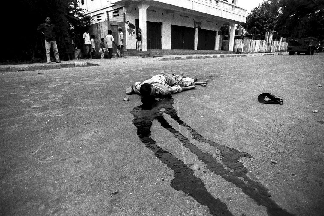 1999年8月26日,東帝汶爭取脫離印尼的獨立公投前四天,爭取獨立團體和爭取一體化的團體之間發生暴動,後者組織民兵,使用大量槍械,圍捕爭取獨立團體。爭取獨立人士Joaquim Bernardino Guterres在衝突中被殺害。據這張照片的攝影師Eddy Hasby回憶,他當時並未看清楚誰殺害了Guterres。而據在同一現場的時代雜誌攝影記者John Stanmeyer回憶,當時Guterres哀求警方介入保護,但警方拒絕,最後倒轉槍頭,將之殺害。Guterres年僅25歲。