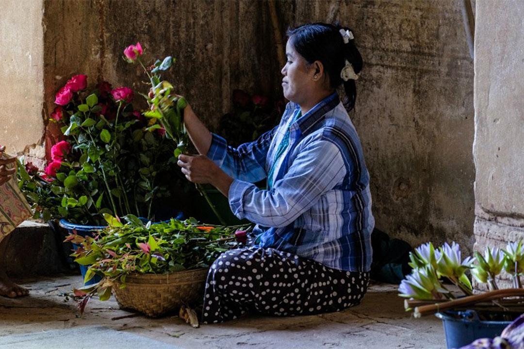 緬甸蒲甘一個佛殿外,有人賣花給前來供佛的人。