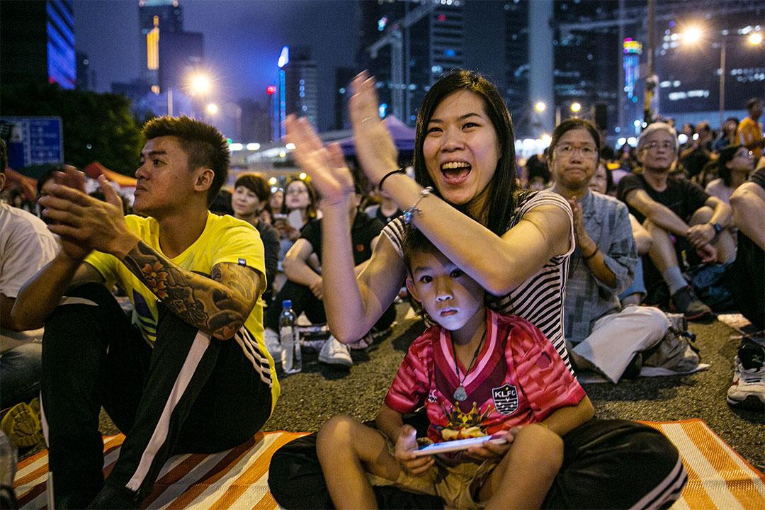 2014年10月18日,在香港,有母親帶同孩子一同於街頭抗議及爭取普選。