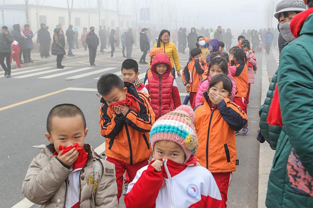 趙亞楠指幼兒園幾乎每天都能聽到孩子啞著嗓子向老師請病假。圖為山東省濱州市,孩子在霧霾下掩著口鼻。