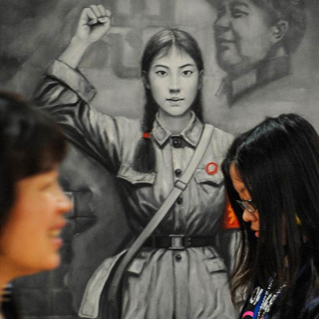 過去於上海舉辦的一個藝術展覽內,一幅文化大革命時期的紅衛兵畫像前,一名年青女孩和一名婦女迎面走過。