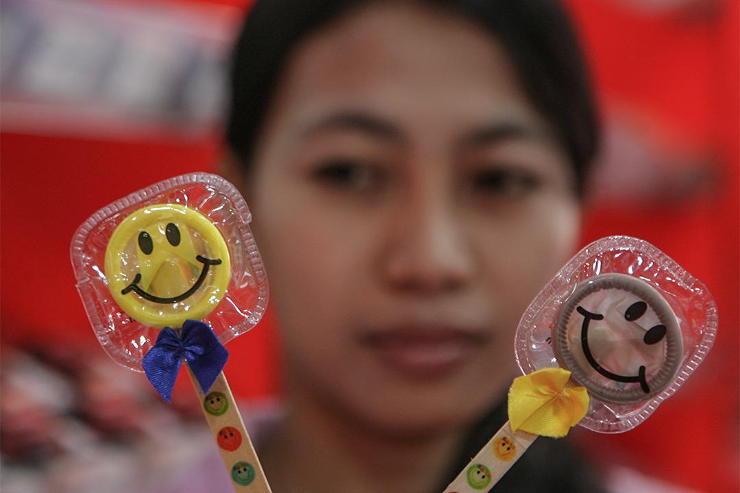 印尼一間性用品店,店員展示店內售賣的保險套。
