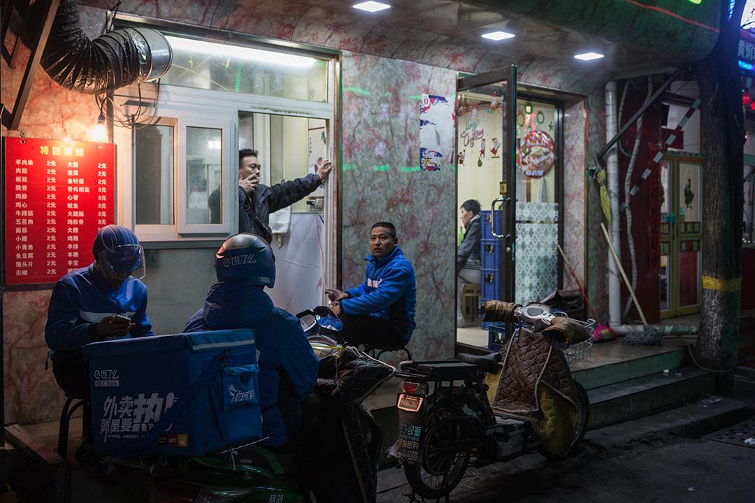 一群外賣員在食店外歇息,等待客人的訂單。