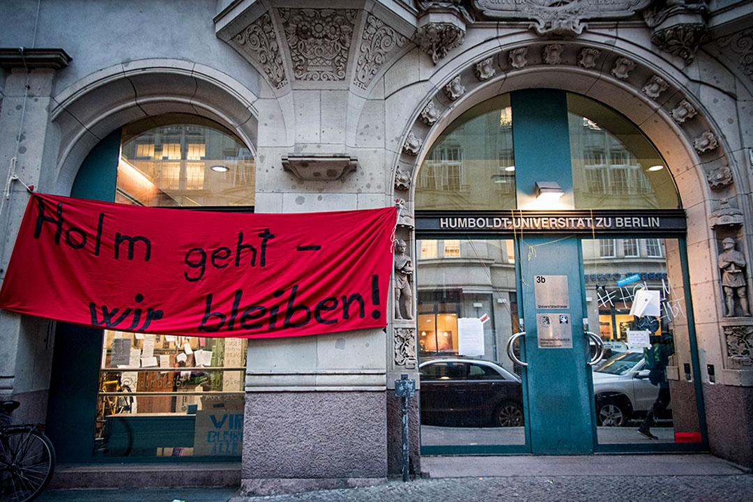 社科院門口垂掛著一塊極度顯眼的紅色布條寫上#HolmBleibt,意為「讓霍爾姆留下來」。