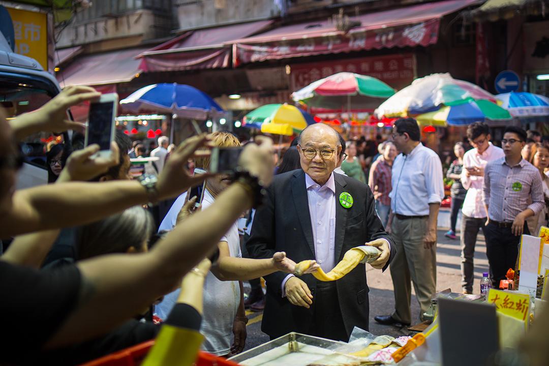 胡國興到旺角街市與市民接觸,市民爭相與他合照。