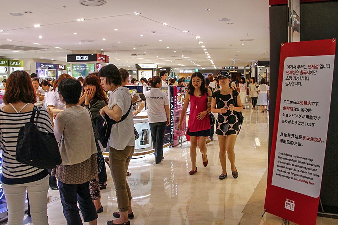 韩国乐天集团2月27日召开董事会,决定把地皮转让给国防部用于部署「萨德」系统。中方对此表示不满。图为中国游客过往于韩国乐天购物。
