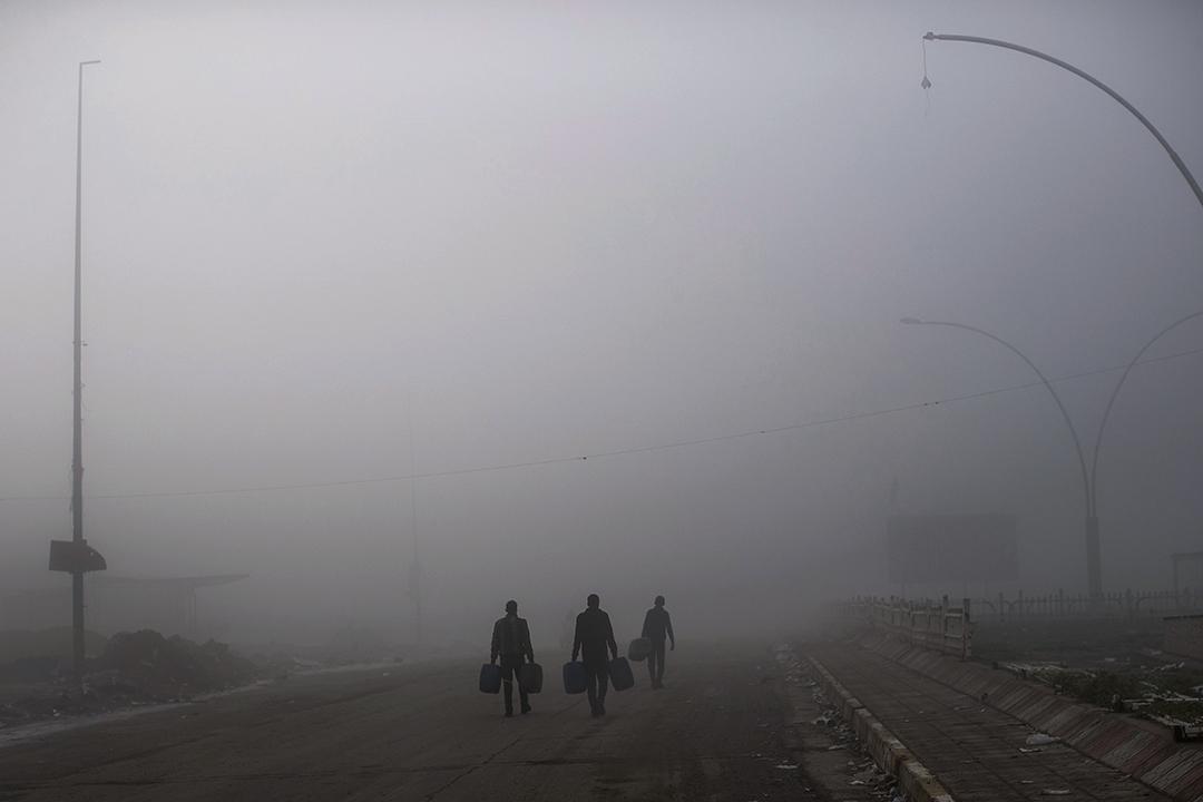 2017年4月2日,伊拉克摩蘇爾西部,幾個人走過濃霧,該區最近由伊拉克安全部隊從伊斯蘭國武裝分子收復。