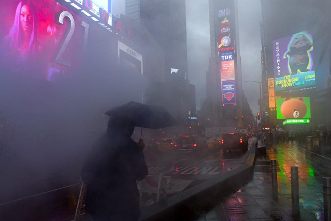 2017年4月6日,一個人在晨雨中穿梭紐約時代廣場。
