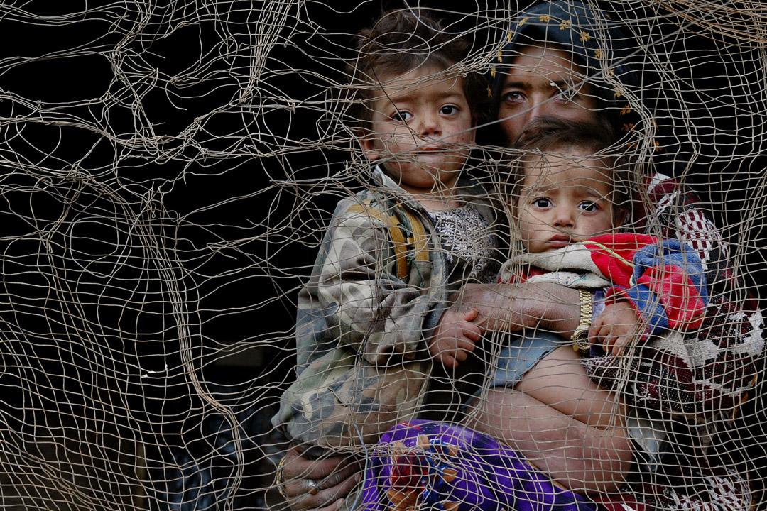 一名母親帶著兩名小孩從洞穴中的居所向望外。許多家庭為了逃離塔利班,流離至被摧毀的巴米揚大佛旁的洞窟中避難,除了這裡,他們已無處安身。