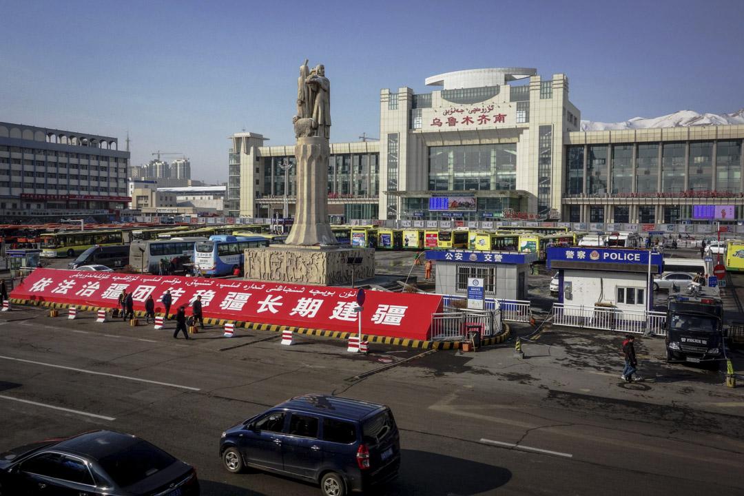 新疆烏魯木齊市火車南站站前廣場,廣場上的治安崗亭、特警防暴車和廣場前的「依法治疆 團結穩疆 長期建疆」巨幅標語格外醒目。
